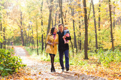 Young family for a walk in the autumn park with Royalty Free Stock Photography