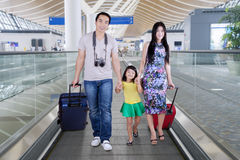 Young family walking on the airport escalator Stock Images