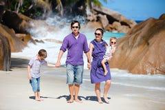 Young family walking along beach Stock Photo