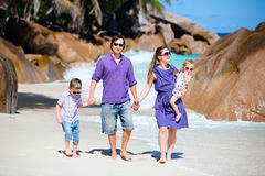 Young family walking along beach royalty free stock photo