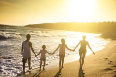 Young family walking on beach at sunset Royalty Free Stock Photo
