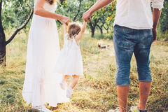 Young family walking in the garden. Mom, Dad, and daughter walk together in the garden Royalty Free Stock Image