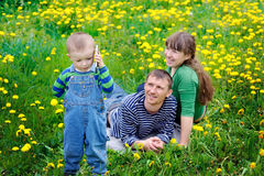 Young family walking on the meadow with yellow flowers in spring Royalty Free Stock Photo