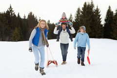 Young Family Walking Through Snow With Sled Royalty Free Stock Photography