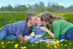 Young family walking on a spring meadow with yellow flowers Stock Photo