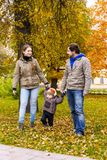 Young family walks with small son in autumn park Royalty Free Stock Images