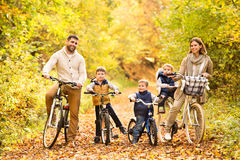 Young family in warm clothes cycling in autumn park. Beautiful young family with three sons in warm clothes cycling outside in autumn nature royalty free stock photos
