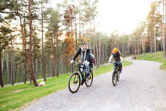 Young family in warm clothes cycling in autumn park Royalty Free Stock Photo