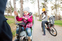 Young family in warm clothes cycling in autumn park Royalty Free Stock Photos