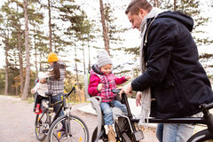 Young family in warm clothes cycling in autumn park Royalty Free Stock Images