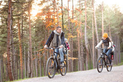 Young family in warm clothes cycling in autumn park Stock Photos