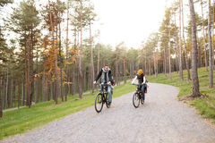 Young family in warm clothes cycling in autumn park Royalty Free Stock Photography