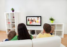 Young family watching TV royalty free stock photo