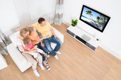Young family watching tv together. At Home Stock Photo