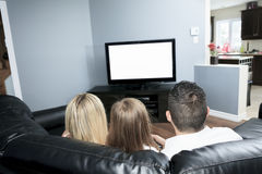 Young family watching TV together at home Stock Images