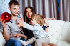 A family with a child sitting on the couch Stock Photos