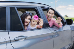 Young family waving hands in car Royalty Free Stock Photo