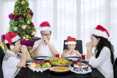 Young family praying before Christmas dinner. Young family wearing Santa hat while praying before Christmas dinner. Shot at home Stock Photography