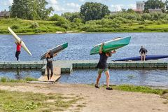 Teenagers go from river and bear kayaks on shoulders, Belarus. Stock Photography