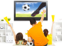 Young fans watching soccer game and yell at home Royalty Free Stock Photo