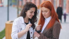 Young fantastic girls in business wear interested in something in smartphone, wind swaying the hair, positive moments stock footage