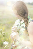 A young farm girl in a flower field with a side braid and plaid shirt. Stock Photo