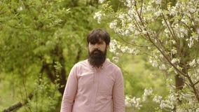 Young farmer bearded man. Portrait of a happy farmer man on green garden background. Farmer concept. Bearded man working stock video