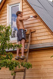 A young farmer is covering primer wall wooden baths Stock Photos