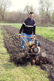 Young farmer cultivates the soil. Young farmer plows a field in spring with motocultivator Stock Images