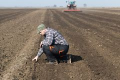 Young farmer dirt while tractor is plowing field stock photos
