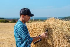 A young farmer in a field with a tablet and a magnifying glass evaluates the hay harvest. Young farmer in field with tablet and magnifying glass evaluates the stock image