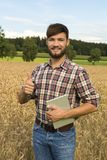 Young farmer at his corn field, thumb up Stock Images