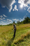 Young farmer mowing grass Stock Image
