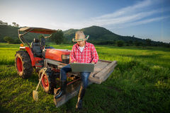 Young Farmer recorded growth of productivity sitting on a tractor. Stock Image