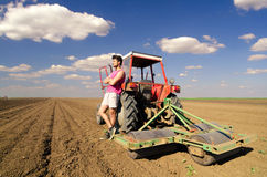 Young farmer resting beside his tractor on agricultural field Royalty Free Stock Photography
