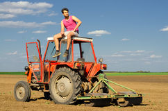 Young farmer resting on top of the tractor on agricultural field Royalty Free Stock Photography