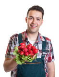 Young farmer showing red radishes Stock Photos