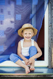 Young farmer sit on the window sill. Outdoor portrait: Young boy sit on the window sill, smiling Stock Images