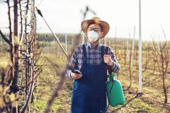 Young farmer spraying the trees with chemicals in the orchard. Young farmer spraying the trees with chemicals in the spring orchard royalty free stock image