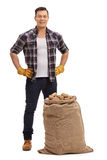Young farmer standing behind burlap sack filled with potatoes. Full length portrait of young farmer standing behind a burlap sack filled with potatoes isolated Stock Photo