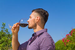 Young farmer tastes a glass of red wine Stock Photos