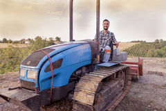 Young farmer toasts on a crawler tractor Stock Images