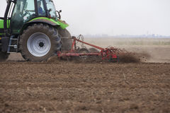 Young farmer in tractor. Autumn sowing preparation at field Stock Photos