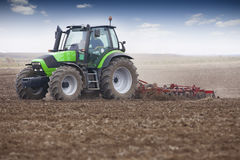 Young farmer in tractor. Field preparation for sowing wheat in autumn Stock Image