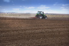 Young farmer in tractor. Tractor preparing land for autumn sowing of wheat Royalty Free Stock Images