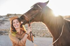 Young farmer woman playing with her horse in a sunny day inside corral ranch - Concept about love between people and animals -