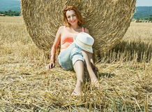 Young farmer woman is sitting and leaning at the haystack during Stock Photos