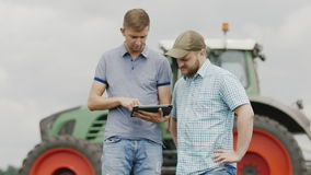 Young farmers communicate in the field, use a tablet. Against the backdrop of agricultural machinery. Two young men of the farmer communicate, use the tablet stock video footage