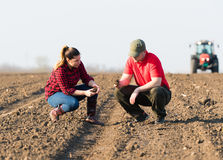Young farmers examing  dirt while tractor is plowing fields Royalty Free Stock Photography