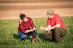 Young farmers examing  planted wheat while tractor is plowing fi Stock Photography